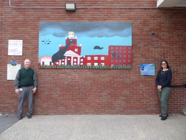 A mural on a brick wall, depicting the city of Dover surrounded by whales, turtles, and other ocean animals as the oceans rise