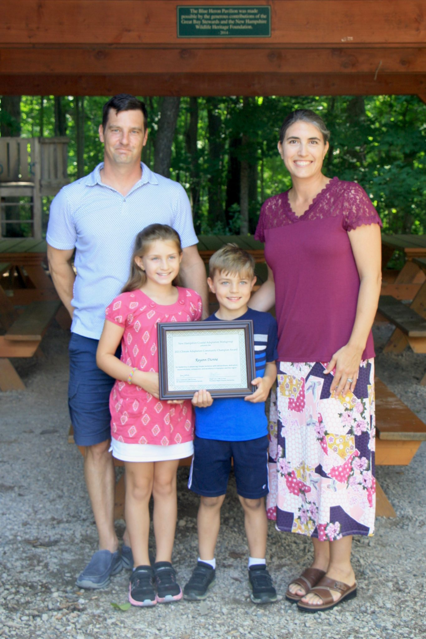 Rayann Dionne with her family (partner and two children holding award)